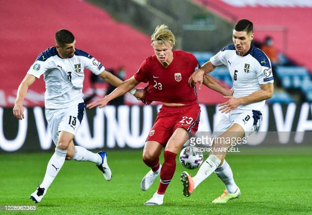 Norway's forward Erling Braut Haaland and Serbia's defender Stefan Mitrovic and Serbia's defender Nikola Milenkovic vie for the ball during the Euro...