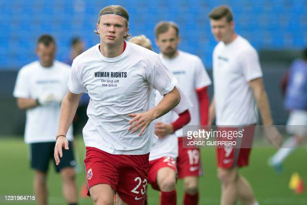 Norway's forward Erling Braut Haaland wears a t-shirt with the slogan 'Human rights, on and off the pitch' as he warms up before the FIFA World Cup...