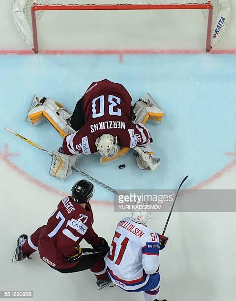 Norway's forward Mats Rosseli Olsen attacks Latvia's goalie Elvis Merzlikins as Latvia's defender Oskars Cibulskis tries to stop him during the group...