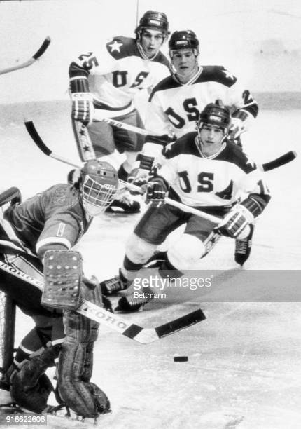 Norway's goalie Jim Martinsen fends off a shot on goal by American, Mark Pavelich as Mark Eruzione and Bill Schneider move up to help.