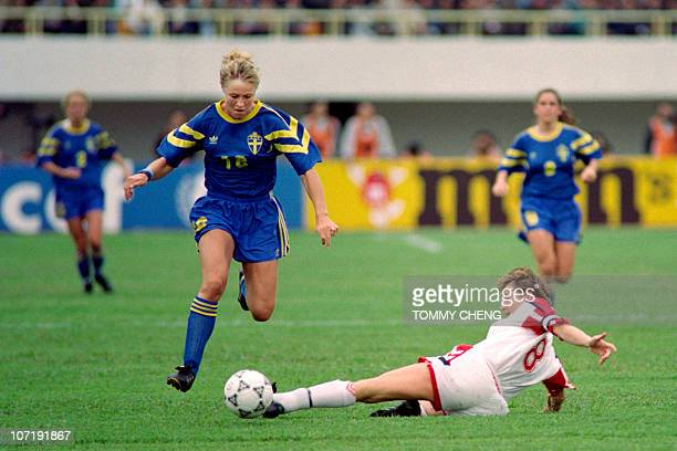 Norway's Heidi Stoere stops the advance of Sweden's Ingrid Johansson during semifinal match in Guangzhou stadium on November 27 at first FIFA World...
