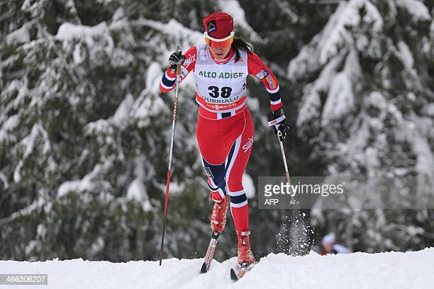 Norway's Heidi Weng competes during the FIS Ski World Cup Ladies' 10 Km Individual Classic race on February 1 2014 in Dobbiaco Norway's Marit...