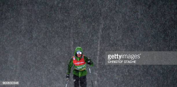 TOPSHOT Norway's Heidi Weng warms up under the heavy rain prior to the ladies' 12 kilometer sprint classic style event of the Tour de Ski Cross...