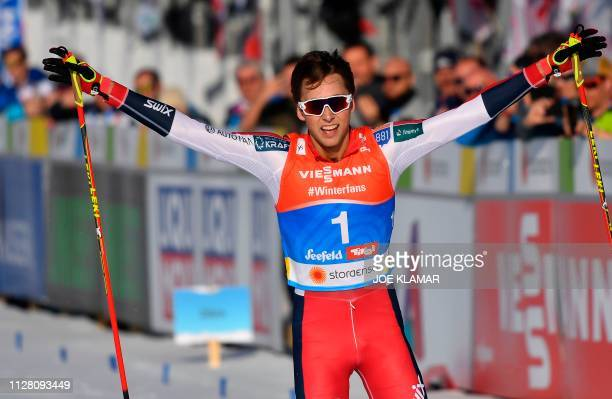 Norway's Jarl Magnus Riiber celebrates after crossing the finish line of the cross-country competition of the men's Nordic Combined Individual...