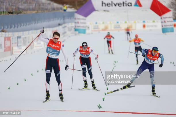 Norway's Jarl Magnus Riiber reacts as he crosses the finish line to win ahead of Finland's Ilkka Herola during the men's 10km individual Gundersen...