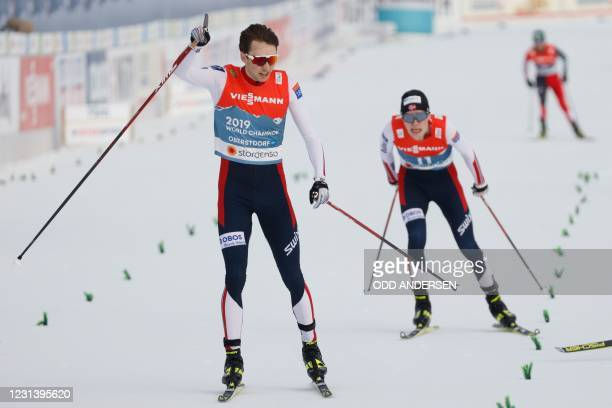 Norway's Jarl Magnus Riiber reacts as he crosses the finish line to win Norway's Jens Luraas Oftebro during the men's 10km individual Gundersen...