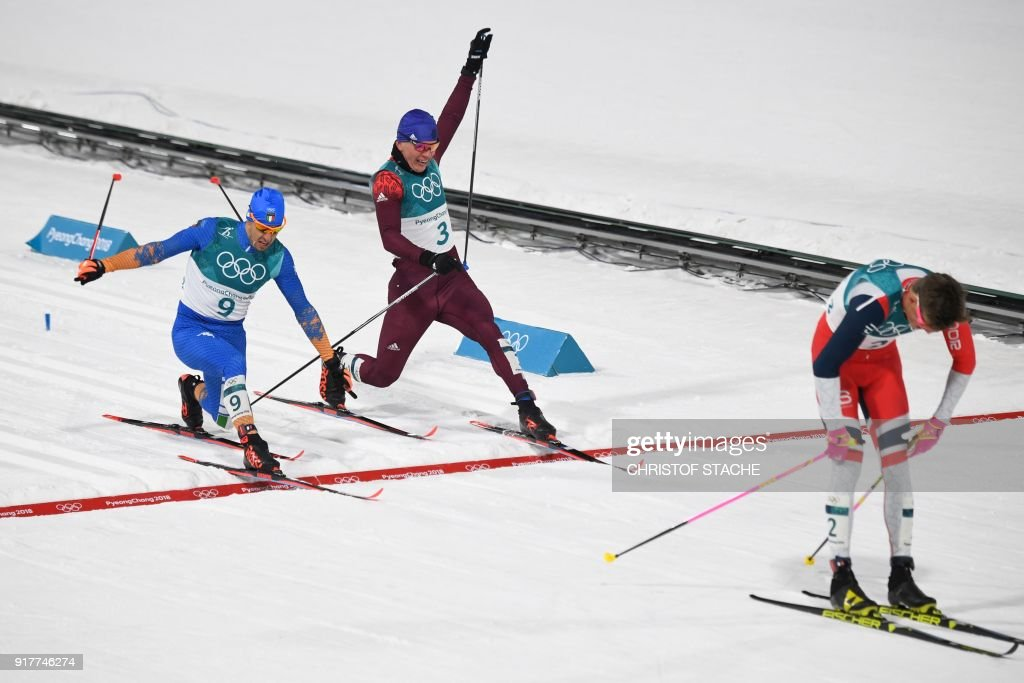 TOPSHOT - Norway's Johannes Hoesflot Klaebo crosses the finish line as Italy's Federico Pellegrino (L) snatches silver and Russia's Alexander Bolshunov, bronze, in the men's cross-country individual sprint classic final at the Alpensia cross country ski centre during the Pyeongchang 2018 Winter Olympic Games on February 13, 2018 in Pyeongchang. / AFP PHOTO / Christof STACHE