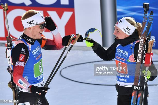 Norway's Johannes Thingnes Boe and Norway's Marte Olsbu Roeiseland celebrate after they won the IBU Biathlon World Cup Single Mixed Relay in...