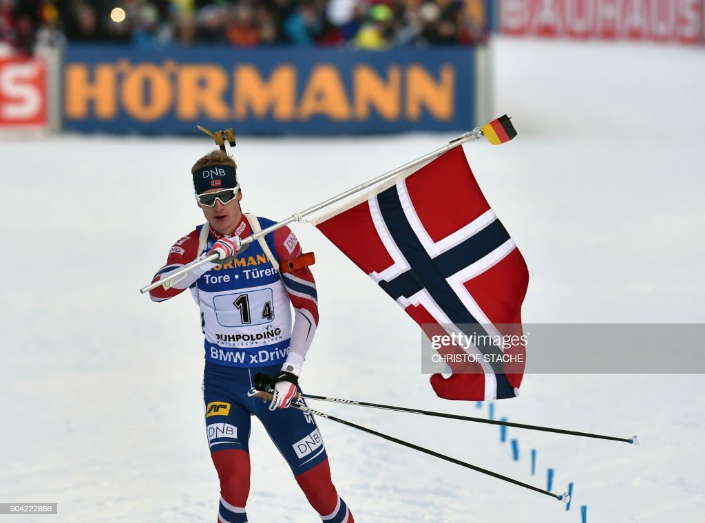 Norway's Johannes Thingnes Boe celebrates with his coutry's flag after the men's 4 x 7,5km relay event at the Biathlon World Cup on January 12, 2018 in Ruhpolding, southern Germany. Norway won the evend ahead of France (2nd) and Russia (3rd). /