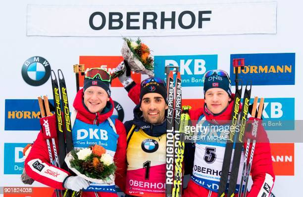 Norway's Johannes Thingnes Boe France's Martin Fourcade and Norway's Tarjei Boe celebrate on the podium after the men's 125 km pursuit event of the...