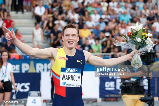 Norway's Karsten Warholm celebrates with a flower bouquet after winning the Men's 400m hurdles during the IAAF Diamond League competition on August...