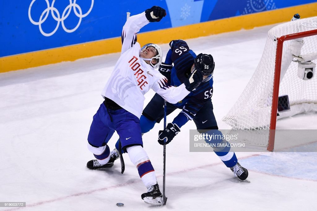 TOPSHOT - Norway's Ken Andre Olimb (L) and Finland's Atte Ohtamaa fight for the puck in the men's preliminary round ice hockey match between Finland and Norway during the Pyeongchang 2018 Winter Olympic Games at the Gangneung Hockey Centre in Gangneung on February 16, 2018. / AFP PHOTO / Brendan Smialowski