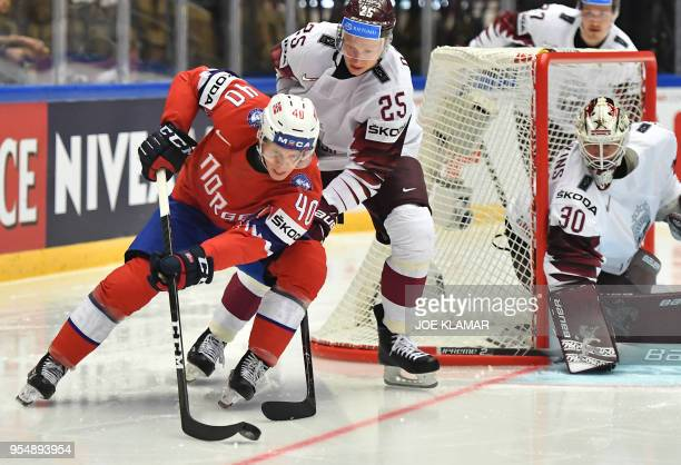 Norway's Ken Andre Olimb challenges for the puck with Latvia's Andris Dzerins as Latvia's goalkeeper Elvis Merzlikins looks on during the group B...