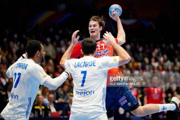 Norway´s Magnus Abelvik Rod jumps to shoot past France's Adrien Dipanda and Romain Lagarde during the Men´s Handball European Championship...