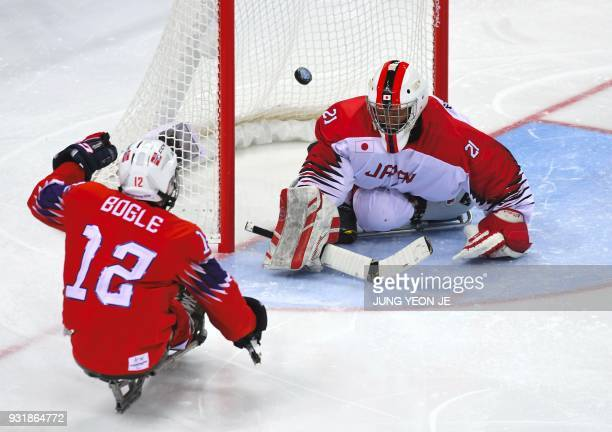 Norway's Magnus Bogle shoots to score a goal against Japan's goalkeeper Shinobu Fukushima during the ice hockey classification game between Norway...