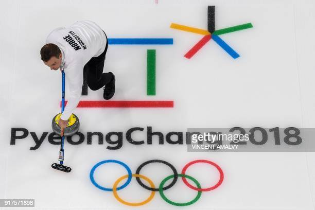 TOPSHOT Norway's Magnus Nedregotten brushes the ice surface during the curling mixed doubles bronze medal game during the Pyeongchang 2018 Winter...