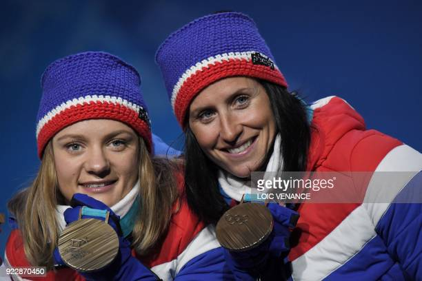 Norway's Marit Bjoergen and Maiken Caspersen Falla pose on the podium during the medal ceremony for the cross country women's free team sprint at the...