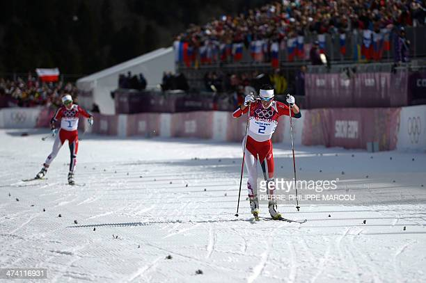 Norway's Marit Bjoergen and Norway's Therese Johaug compete to the finish line in the Women's CrossCountry Skiing 30km Mass Start Free at the Laura...
