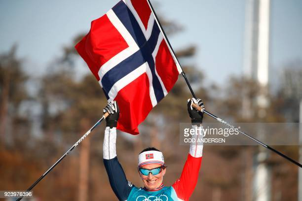 TOPSHOT Norway's Marit Bjoergen celebrates her gold medal win in the women's 30km cross country mass start classic at the Alpensia cross country ski...