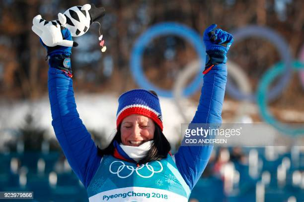 TOPSHOT Norway's Marit Bjoergen celebrates her gold win on the podium during the venue ceremony for the women's 30km cross country mass start classic...