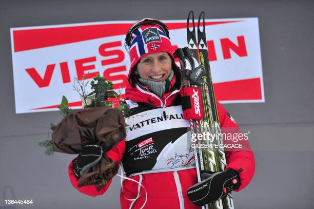 Norway's Marit Bjoergen celebrates on the podium after winning the 15 km free pursuit of the seventh stage of the ladies' Nordic Skiing Tour de Ski...