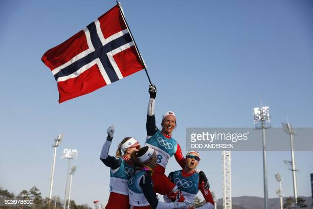 TOPSHOT Norway's Marit Bjoergen is lifted by her compatriots as she waves the Norwegian flag after winning gold in the women's 30km cross country...