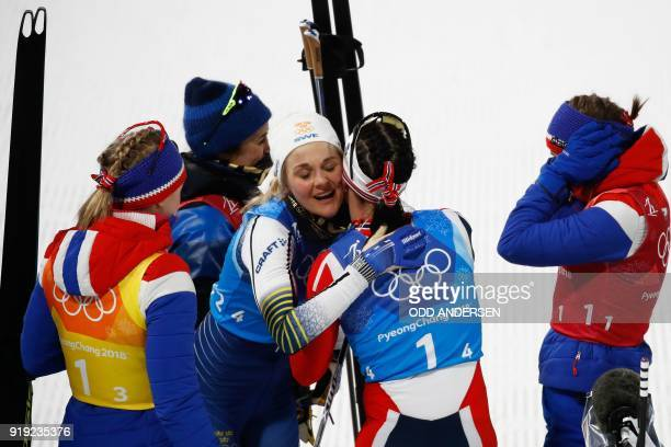 Norway's Marit Bjorgen is congratulaed by Sweden's Stina Nilsson after the women's 4x5km classic free style cross country relay at the Alpensia cross...