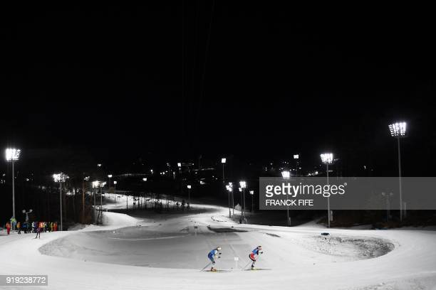 TOPSHOT Norway's Marit Bjorgen leads ahead of Sweden's Stina Nilsson during the women's 4x5km classic free style cross country relay at the Alpensia...