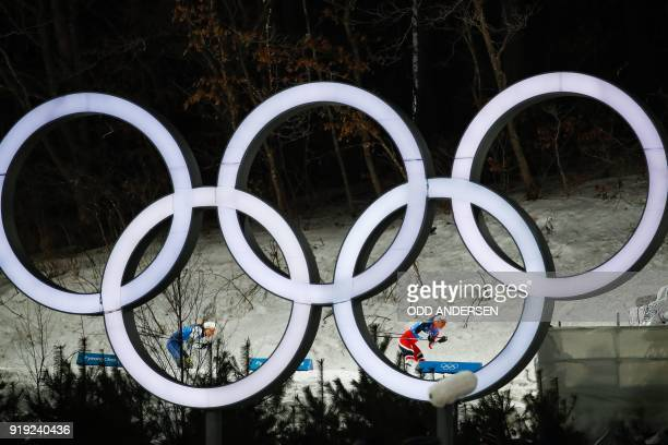 TOPSHOT Norway's Marit Bjorgen leads ahead of Sweden's Stina Nilsson seen through the Olympic rings during the women's 4x5km classic free style cross...