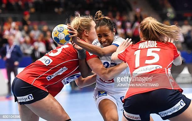 Norway's Marit Malm Frafjord and Silje Waade vie with France's Estelle Nze Minko during the Women's European Handball Championship semi final match...