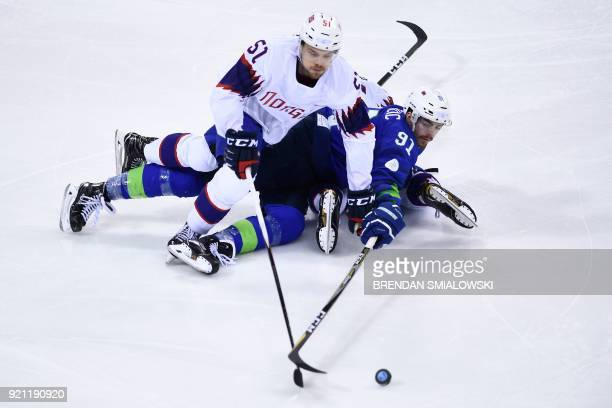 TOPSHOT Norway's Mats Rosseli Olsen and Slovenia's Miha Verlic vie for the puck during the second period of a men's quarterfinals playoffs ice hockey...