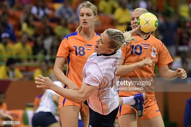 Norway's pivot Heidi Loke jumps to shoot past Netherlands' left back Kelly Dulfer and Netherlands' pivot Danick Snelder during the women's Bronze...