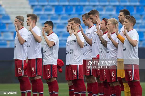 """Norway's players pose with t-shirts reading """"Human rights, on and off the pitch. Norway, Germany, next?"""" in support of migrant workers building World..."""