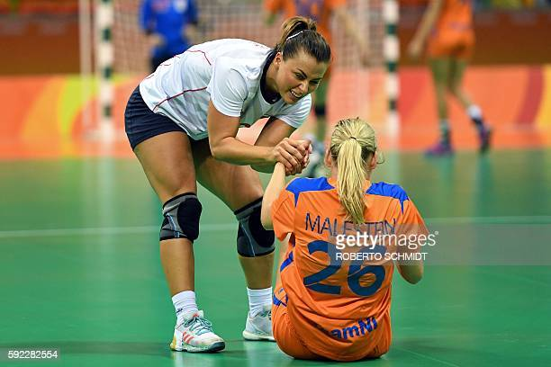 Norway's right back Nora Mork helps Netherlands' right wing Angela Malestein to satnds up after a fall during the women's Bronze Medal handball match...