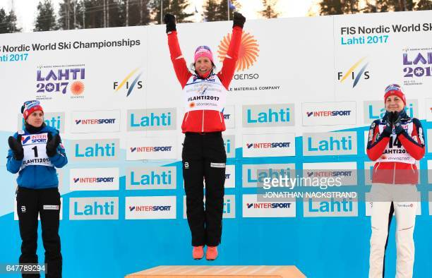 Norway's second placed Heidi Weng winner Marit Bjoergen and third placed Astrid Uhrenholdt Jacobsen celebrate on the podium of the ladies'...
