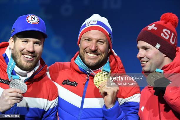 Norway's silver medallist Kjetil Jansrud Norway's gold medallist Aksel Lund Svindal and Switzerland's bronze medallist Beat Feuz pose on the podium...