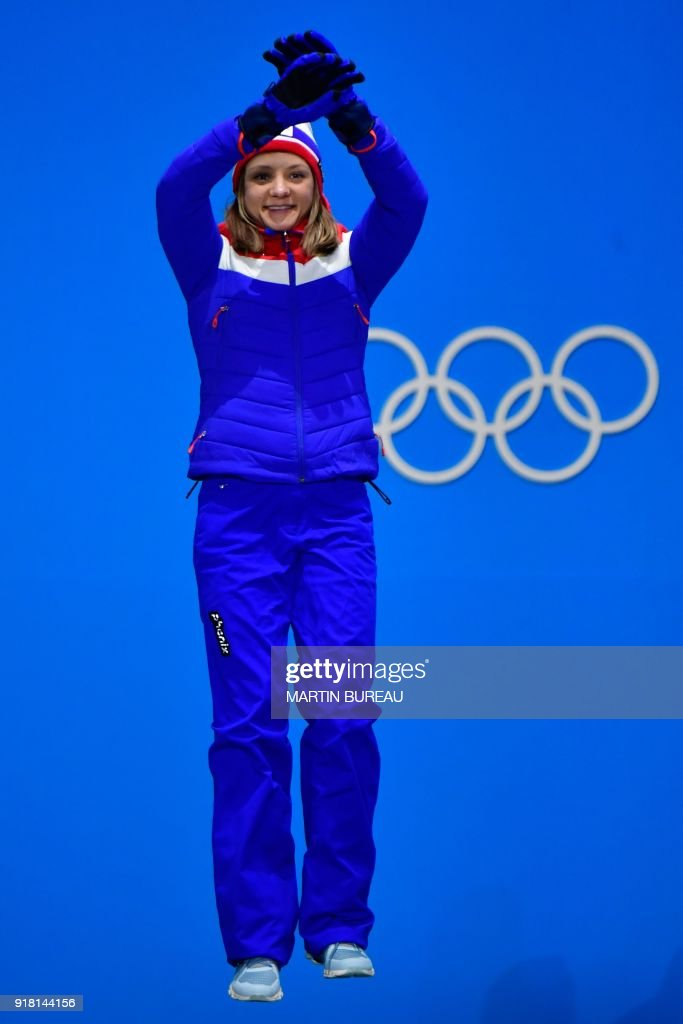 Norway's silver medallist Maiken Caspersen Falla jumps on the podium during the medal ceremony for the women's cross country sprint classic at the Pyeongchang Medals Plaza during the Pyeongchang 2018 Winter Olympic Games in Pyeongchang on February 14, 2018. / AFP PHOTO / Martin BUREAU