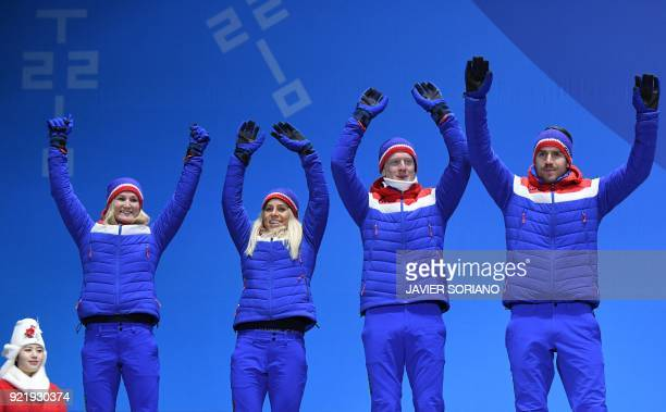Norway's silver medallists Marte Olsbu Tiril Eckhoff Johannes Thingnes Boe and Emil Hegle Svendsen pose on the podium during the medal ceremony for...