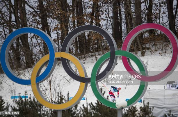 TOPSHOT Norway's Simen Hegstad Krueger is seen behind the Olympic rings as he comes imnto to the stadium on the last lap to win the men's 15km 15km...