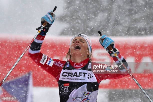 Norway's Therese Johaug celebrates as she crosses the finish line of the 9 km climb pursuit and the Tour de Ski during the 7th stage of the ladie's...