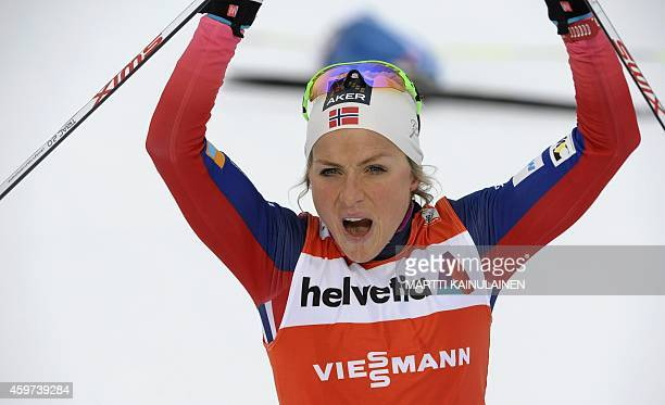 Norway's Therese Johaug celebrates as she crosses the finish line to win the women's cross country 10 km classic style skiing competition at the FIS...