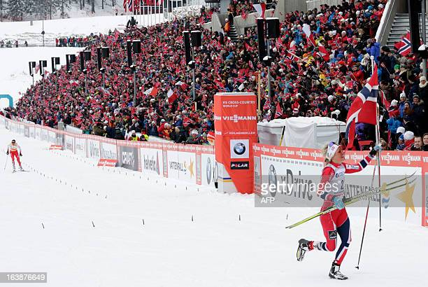 Norway's Therese Johaug celebrates while Poland's Justyna Kowalczyk approaches the finishing line at the ladies Holmenkollen Cross Country 30 km...