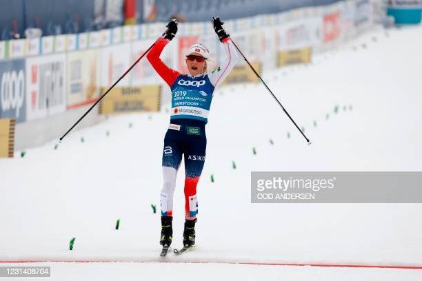 Norway's Therese Johaug celebrates winning as she crosses the finish line of the Women' Skiathlon 2x7,5km event at the FIS Nordic Ski World...