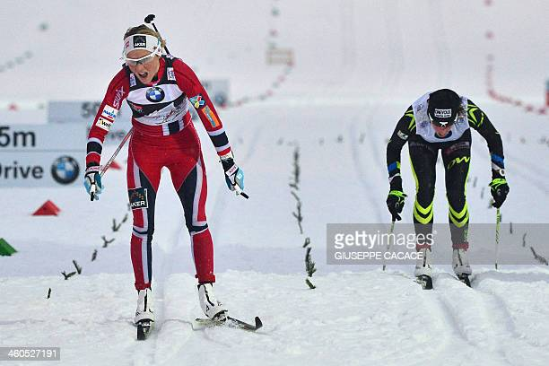 Norway's Therese Johaug crosses the finish line in front of Coraline Hugue of France during the 5km Classic of the sixth stage of the ladies Nordic...