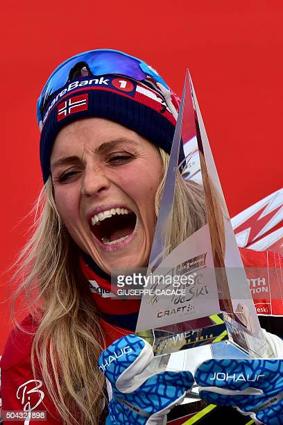 Norway's Therese Johaug reacts as she holds her trophy on the podium after winning the Women's 9 km Climb Pursuit of the FIS World Cup Tour de Ski at...