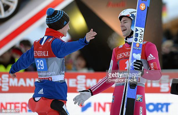 Norwegian Anders Fanemel congratulates his teammate Norwegian Anders Jacobsen after the second competition jump of the second session of the...