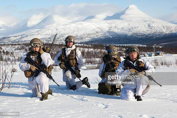 Norwegian army medical team observes a live fire exercise March 6 2013 during a 8 F degree windblown day in Skjold Norway White camouflage uniforms...