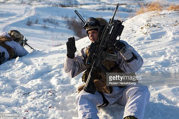 Norwegian army soldier communicates during a live fire exercise March 6 2013 in Skjold Norway White camouflage uniforms do not completely help...