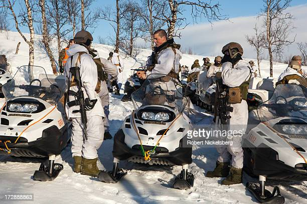 Norwegian army soldiers use snowmobiles for mobility during a live fire exercise March 6 2013 in Skjold Norway White camouflage uniforms do not...