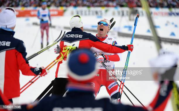 Norwegian athlete Finn Haagen Krogh reacts with teammates after competing in the men's 4 x 10 kilometre relay race at the Nordic Ski World...